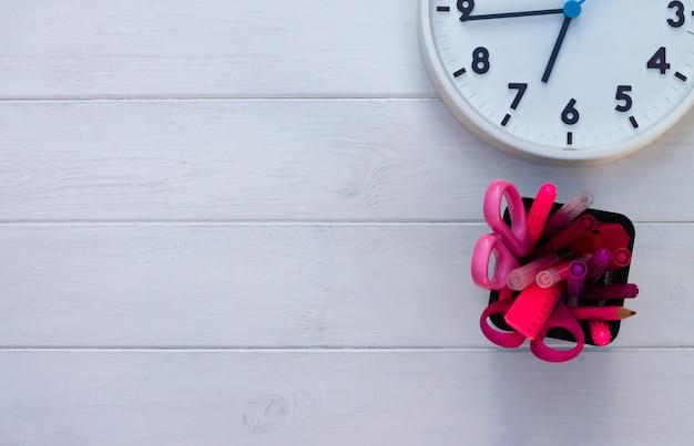 Fournitures scolaires roses et horloge sur un fond en bois blanc. vue de dessus. espace de copie. concept d'éducation et de retour à l'école.