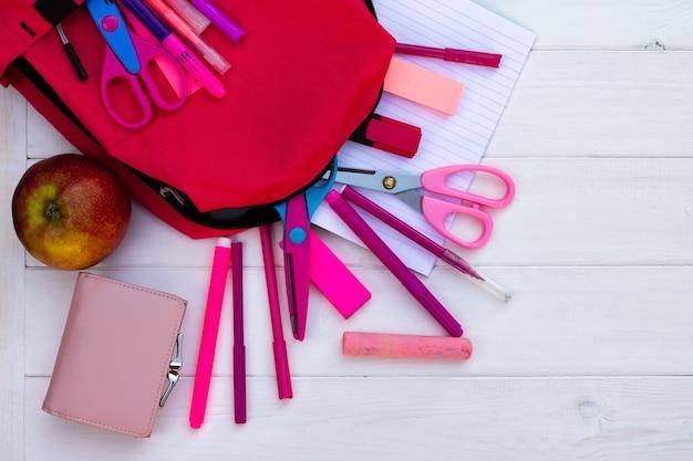 Fournitures scolaires roses et sac à dos sur fond en bois blanc. vue de dessus. espace de copie. concept d'éducation et de retour à l'école.
