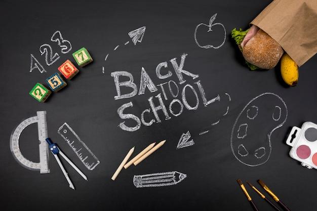 Fournitures scolaires et sandwich sur tableau noir