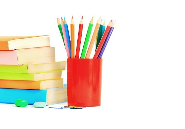 Les fournitures scolaires se trouvent sur une table sur un fond blanc