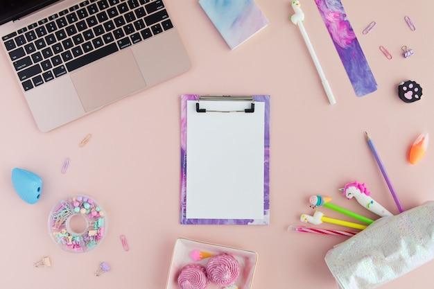 Fournitures scolaires avec un stylo licorne, un crayon lama et un ordinateur portable en rose.