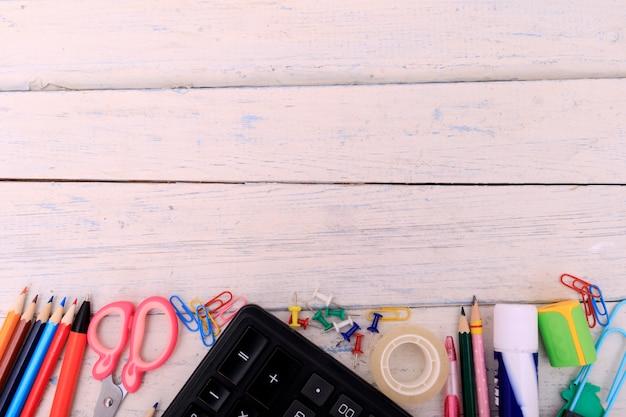Fournitures scolaires sur une table en bois blanche.
