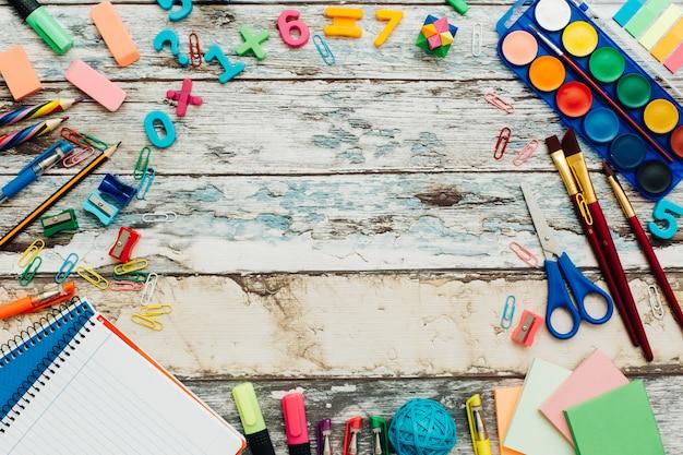Fournitures scolaires sur une table en bois rustique.