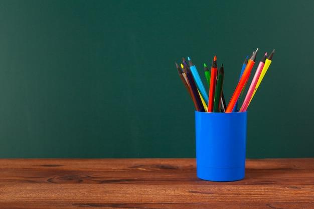 Fournitures scolaires sur une table en bois et tableau noir