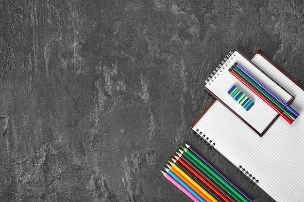 Fournitures scolaires sur une table grise avec un espace pour le texte, vue de dessus.