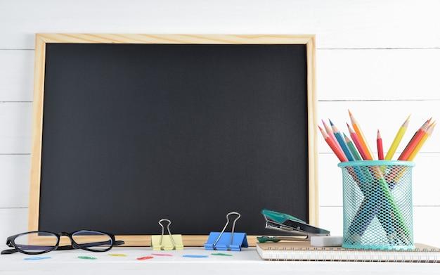 Fournitures scolaires sur tableau noir et bois blanc