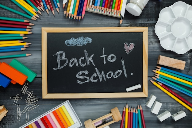 Fournitures scolaires sur tableau noir. retour au concept de l'école.