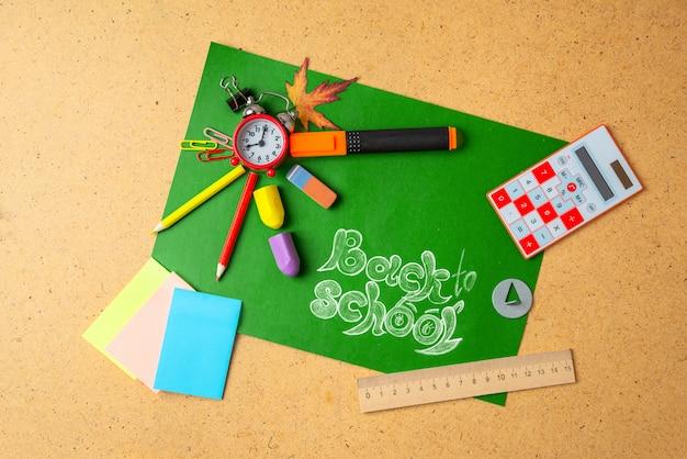 Fournitures scolaires sur tableau vert.