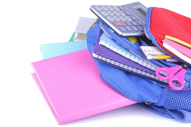 Fournitures scolaires tombant d'un sac à dos sur un fond blanc isolé