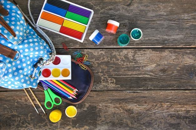 Les fournitures scolaires tombent du sac à dos sur la vieille table en bois. vue de dessus.