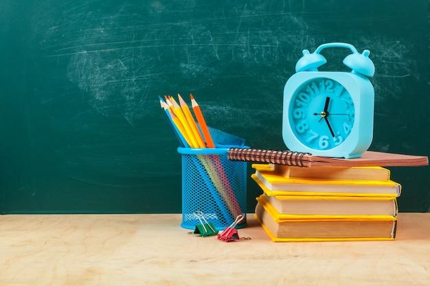 Fournitures scolaires. ustensiles d'écriture et réveil. temps d'étudier le concept