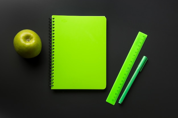 Fournitures scolaires vertes, cahiers sur fond noir vue de dessus