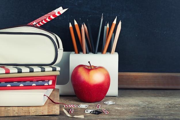 Fournitures scolaires sur la vieille table en bois, près du tableau noir, gros plan