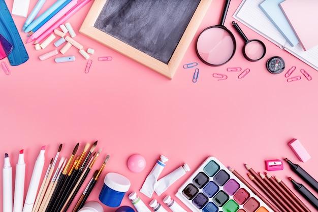 Fournitures scolaires sur vue de dessus rose, mise à plat