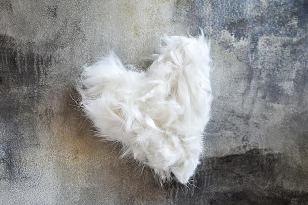 La fourrure blanche cisaillée de l'animal est disposée en forme de coeur sur fond de béton gris. s'occuper d'un animal