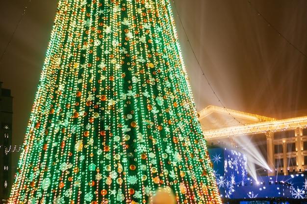 Fragment d'arbre de noël décoré sur la place de la ville la nuit, avec des faisceaux de projecteurs