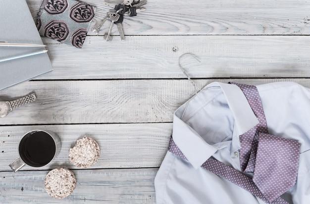 Fragment d'une chemise pour homme avec une cravate sur un cintre, des craquelins, une tasse à café sur une surface en bois peinte. les couleurs pastel