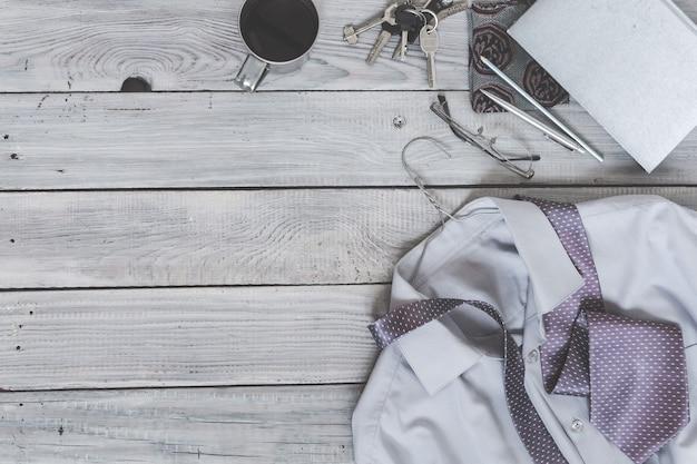 Fragment d'une chemise pour homme avec une cravate sur un cintre, un journal intime, une tasse à café sur une surface en bois peinte. les couleurs pastel