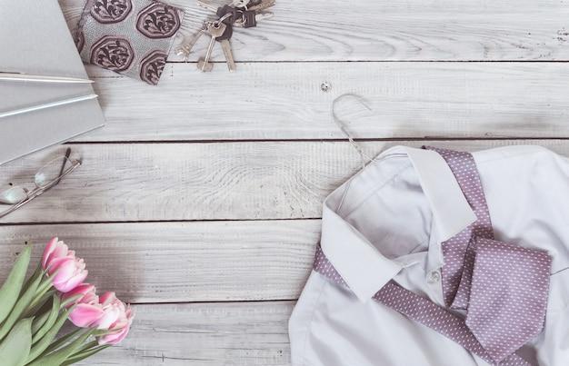 Fragment d'une chemise pour homme avec une cravate sur un cintre, un journal intime, des tulipes sur une surface en bois peinte. les couleurs pastel