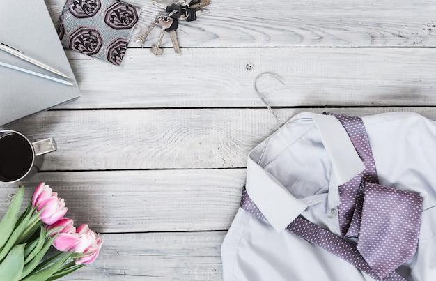 Fragment d'une chemise pour homme avec une cravate sur un cintre, des tulipes, une tasse à café sur une surface en bois peinte. les couleurs pastel