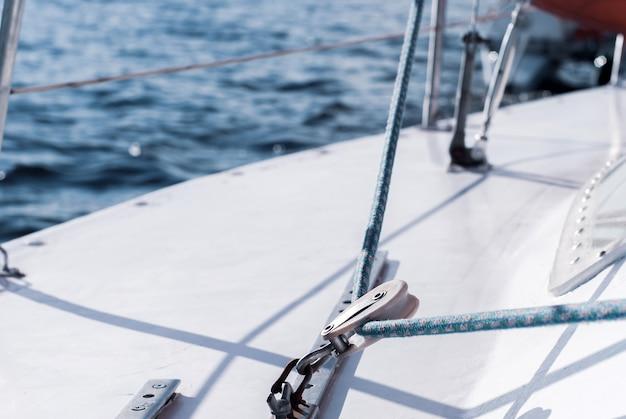 Fragment de la coque d'un voilier avec gréement sur fond d'eau