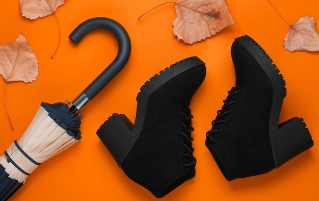 Fragment de crochet de parapluie, de bottes et de feuilles mortes sur fond orange. vue de dessus. accessoires d'automne. mise à plat