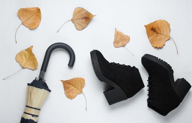 Fragment de crochet parapluie, bottes et feuilles tombées sur tableau blanc. vue de dessus. accessoires d'automne. mise à plat