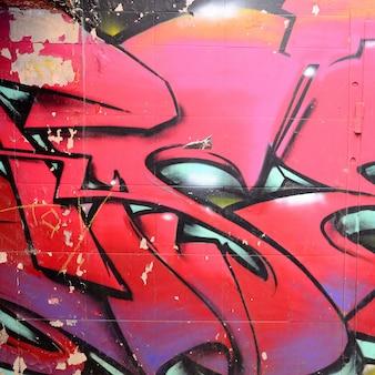 Fragment de dessins graffitis. le vieux mur décoré de taches de peinture dans le style de la culture street art.