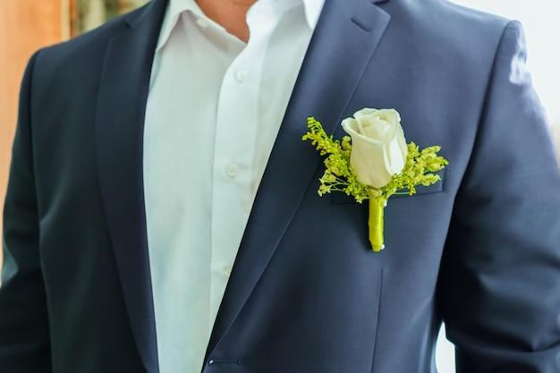 Un fragment du torse de l'homme du marié dans une veste bleue et une chemise blanche avec une boutonnière rose blanche