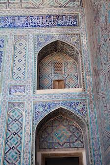 Un fragment de la façade d'une madrasa décorée de mosaïques sur la place du registan à samarkand, ouzbékistan.
