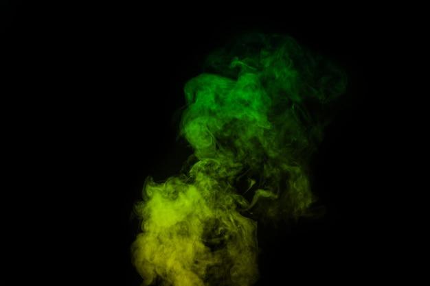 Fragment de fumée de vapeur bouclée jaune verte isolée sur fond noir, gros plan. créez des photos d'halloween mystiques. abstrait, élément de conception