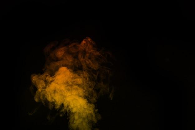 Fragment de fumée de vapeur jaune orange isolé sur fond noir, gros plan. créez des photos d'halloween mystiques. abstrait, élément de conception