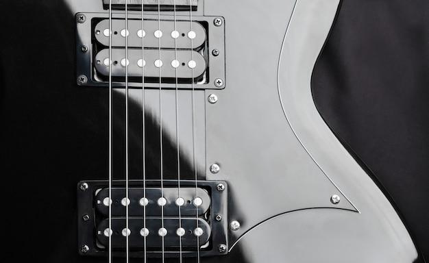 Un fragment d'une guitare noire avec des cordes en acier