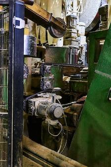 Fragment de l'intérieur de l'atelier d'une scierie moderne avec équipement recouvert d'une couche de sciure de bois