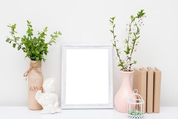 Un fragment de l'intérieur avec un cadre photo blanc (maquette), des vases et des livres