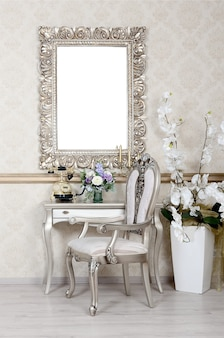 Un fragment d'un intérieur rétro avec une chaise et une table, sur lequel se trouvent un téléphone et un vase de fleurs