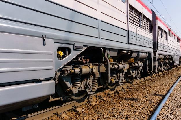 Fragment d'une locomotive moderne ensoleillée sur une voie avec des châssis de camion s'étendant en perspective
