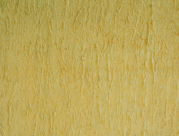 Fragment de mur de ciment jaune, structure ondulée