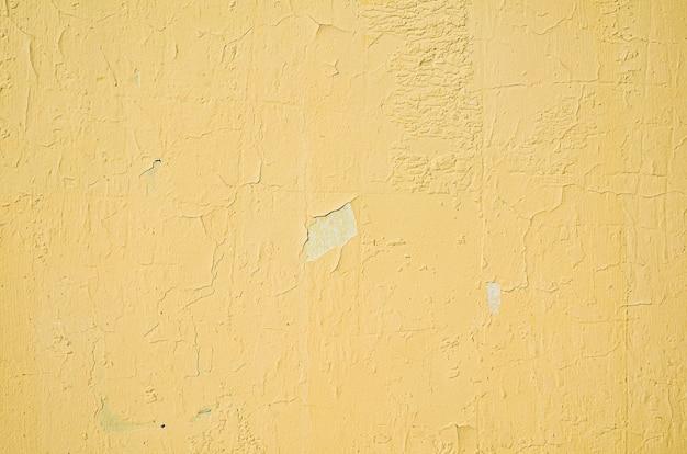 Fragment de mur jaune avec des rayures et des fissures de la peinture de mur jaune fissurée grungy qui se décolle de la vieille peinture qui s'écaille de fond de texture de mur