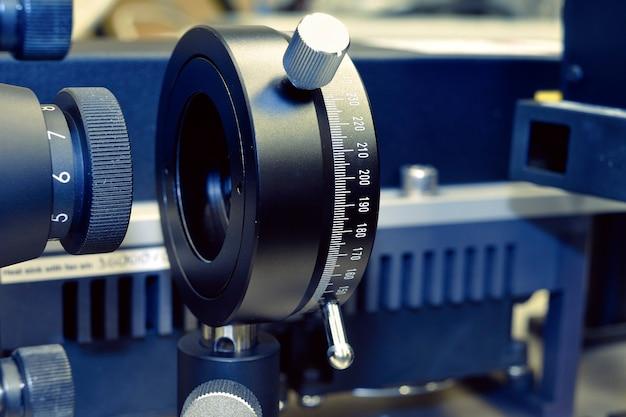Fragment optomécanique abstrait à l'intérieur du laboratoire d'optique; mise au point sélective sur la plaque avec des chiffres