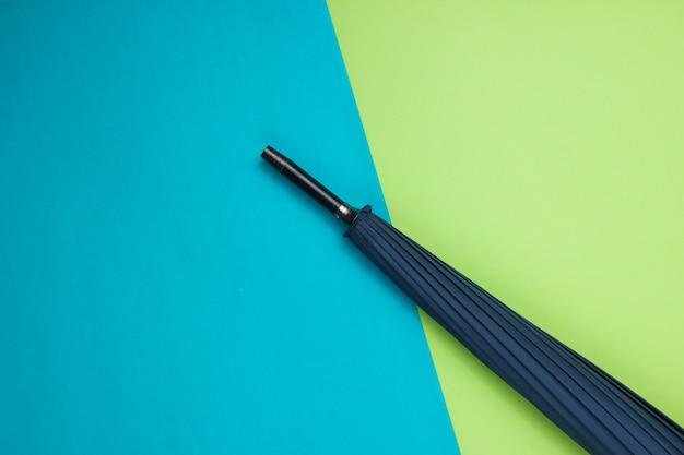 Fragment d'un parapluie sur une table vert-bleu. vue de dessus
