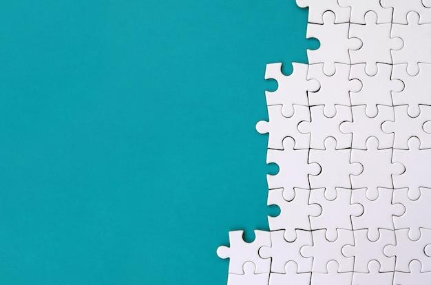 Fragment d'un puzzle blanc plié sur le fond d'une surface en plastique bleue