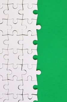 Fragment d'un puzzle blanc plié sur le fond d'une surface en plastique verte.
