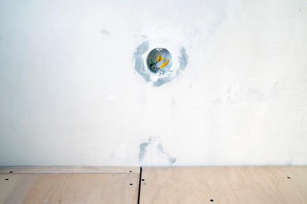Fragment de rénovation intérieure avec mur blanc avec boîtier électrique ouvert et plancher en contreplaqué