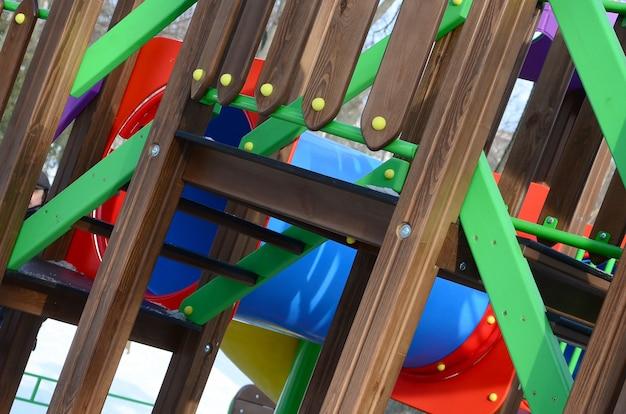 Fragment d'un terrain de jeu en plastique et bois, peint de différentes couleurs
