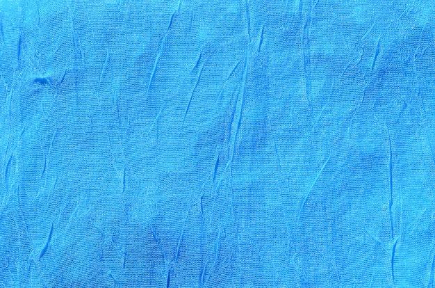 Fragment de tissu bleu froissé comme texture de fond