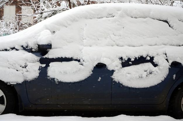 Fragment de la voiture sous une couche de neige après une forte chute de neige. le corps de la voiture est recouvert de neige blanche