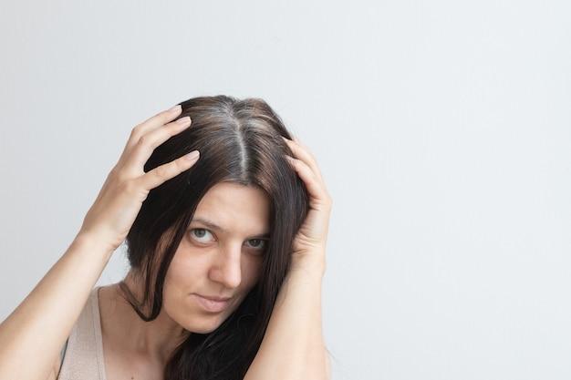 Fragments de cheveux gris sur la tête d'une jeune femme concept de cheveux gris au début