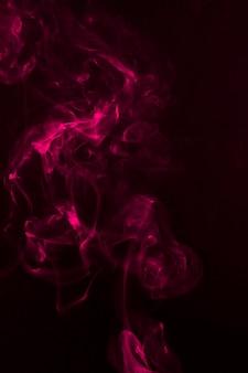 Fragments de fumée rose sur fond noir