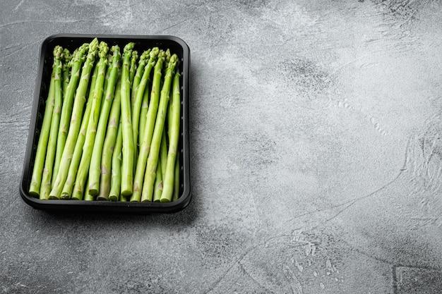 Frais d'asperges vertes. cuisiner un repas sain. bouquets d'asperges vertes, ensemble dans un récipient de marché en plastique, sur table en pierre grise
